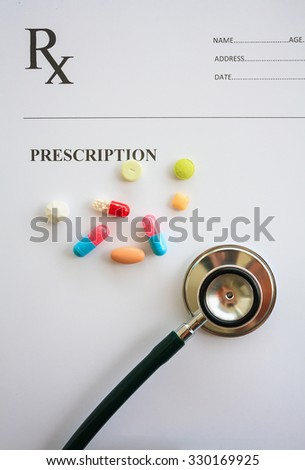 Pills and stethoscope on a prescription - stock photo