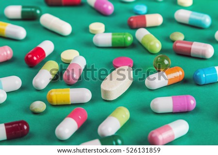 pills and tablets of different colors background.