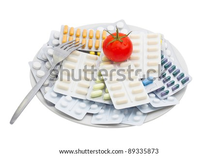 Pills and tablets with tomato on plate, isolated on white background.