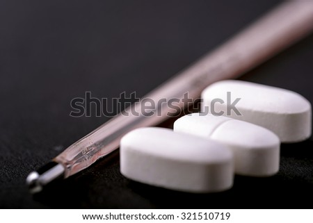 pills and thermometer for flu concept on black background