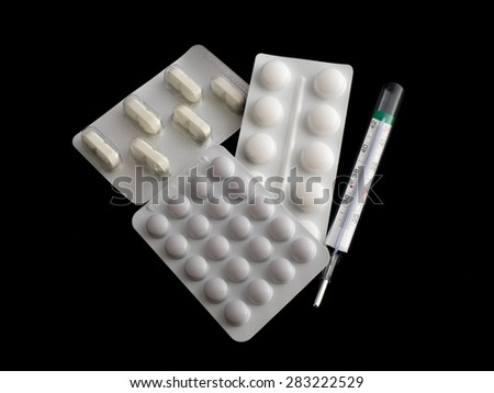 Pills and thermometer isolated on black background