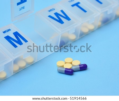 Pills and weekly container - stock photo