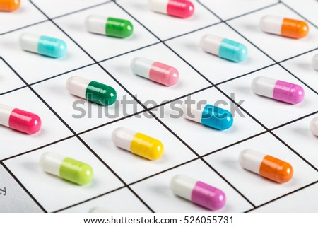 pills are of different color on a light background. Focus on a green pill