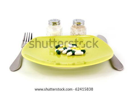 pills as dinner on plate on white background - stock photo