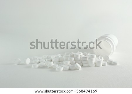 Pills aspirin from a container on isolated background - stock photo