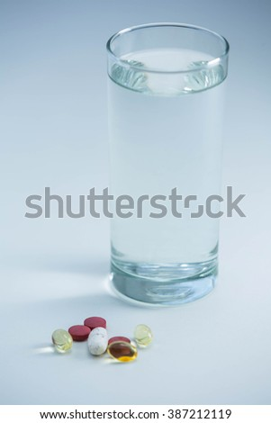 Pills beside glass of water on table