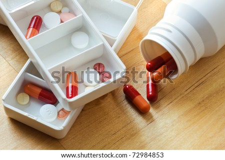 Pills, capsules and tablets sorted in medicine box for use as daily medication - stock photo