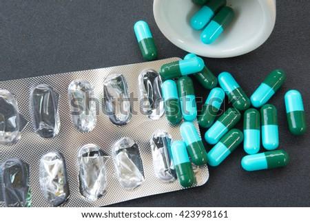 pills capsules medicine on black table - stock photo