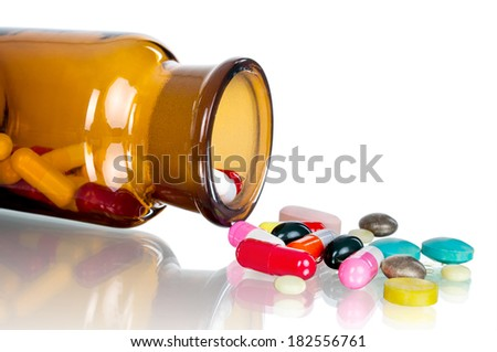 Pills from bottle on the white - stock photo