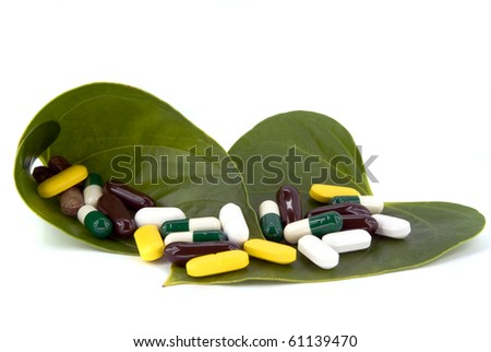 pills in green leaf on white background - stock photo
