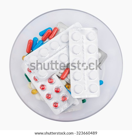 Pills lying blister packed in a bowl. Isolated on white background. - stock photo