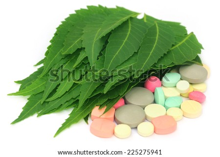 Pills made from medicinal neem leaves over white background