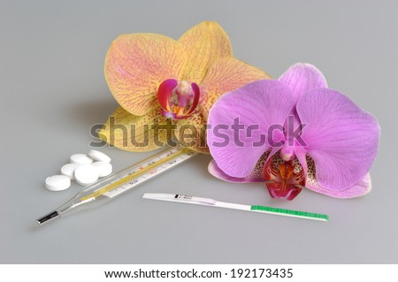 Pills, mercury thermometer and ovulation test with two orchid flowers on gray - stock photo