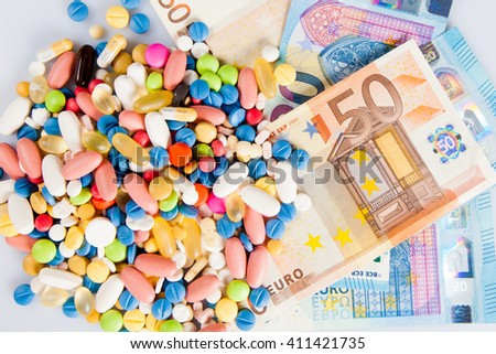 Pills of different colors on money - stock photo