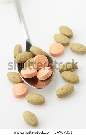 Pills of vitamin C and nutritional supplements in spoon on white background.