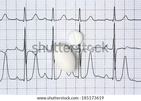 Pills on a background of electrocardiogram ECG cardiology disease - stock photo