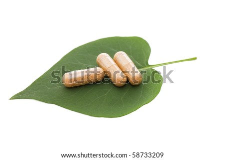 Pills on green sheet isolated on white - stock photo
