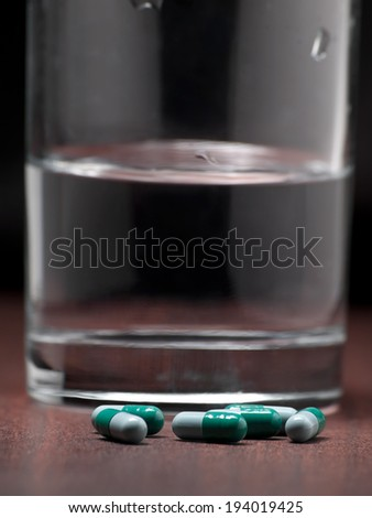 Pills on the night table with glass of water in the background,for medicine,health,addiction themes - stock photo