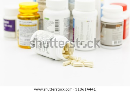 Pills on the white background with medicine bottle - stock photo