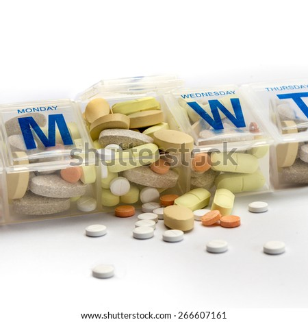 Pills or supplements spill out of a crammed weekly pill box - stock photo