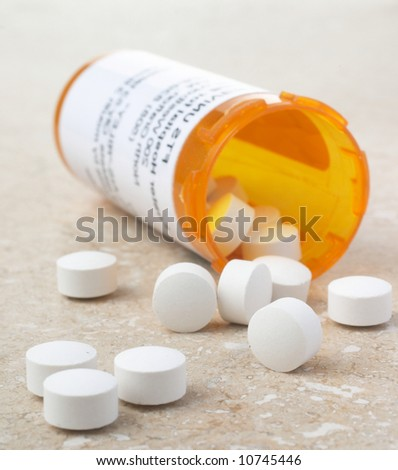 Pills out of medicine bottle - stock photo