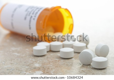 Pills out of presciption bottle - stock photo