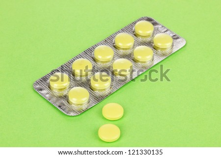Pills packed in blister on green background