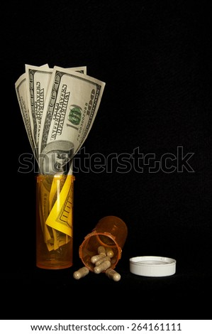Pills, pill bottles, lid and cash - stock photo