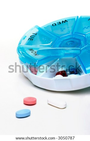 Pills planner with weekly amount of medication capsules in it and few near - stock photo