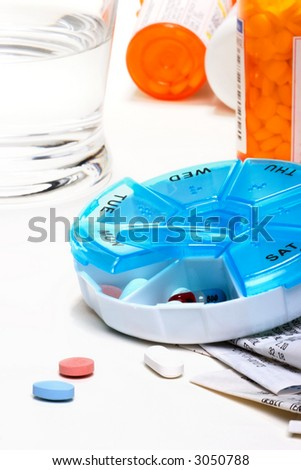 Pills planner with weekly medication capsules in it, glass of water and set of receipts - stock photo