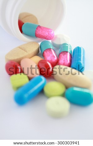 Pills pouring from white bottle on white background
