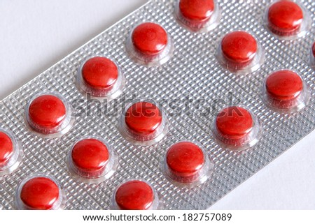 Pills red in blister on  white background - stock photo