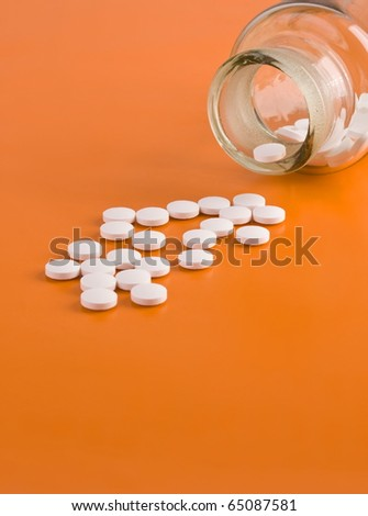 Pills spilled from a pill bottle on orange background - stock photo