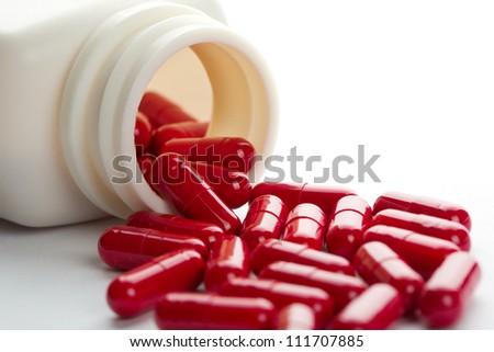 Pills spilling from an open bottle - stock photo