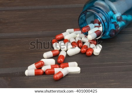 Pills spilling from an open bottle. Doping in sport. Abuse of anabolic steroids for sports. Anabolic steroids spilled on a wooden table. Food supplements in the diet. - stock photo