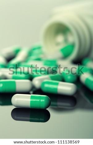Pills spilling from an open bottle. Toned - stock photo