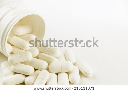 Pills spilling from container. Copy space - stock photo