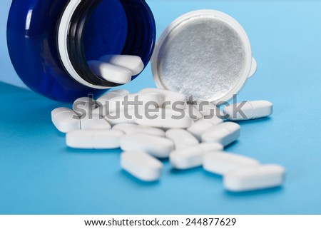 Pills Spilling Out Of A Prescription Bottle Over Blue Background - stock photo
