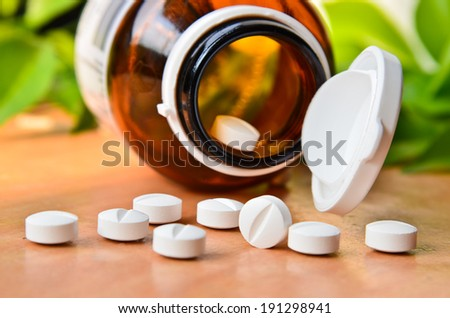 Pills Spilling out of Pill Bottle - stock photo