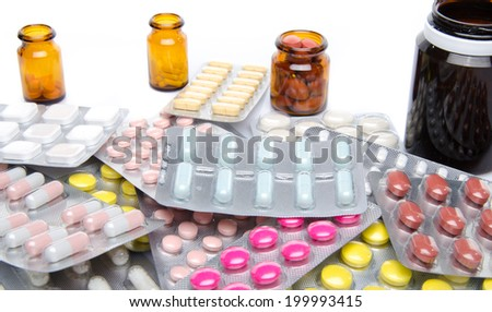 Pills, tablets and capsules in blister packs and bottles, isolated on white