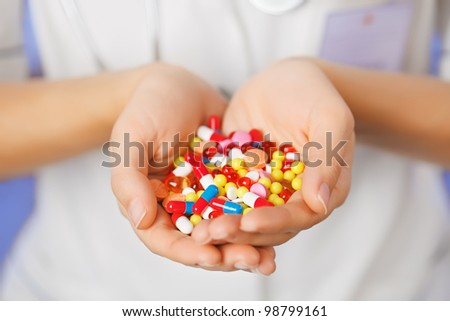 Pills, tablets and drugs heap in doctor's hand on blue background - stock photo