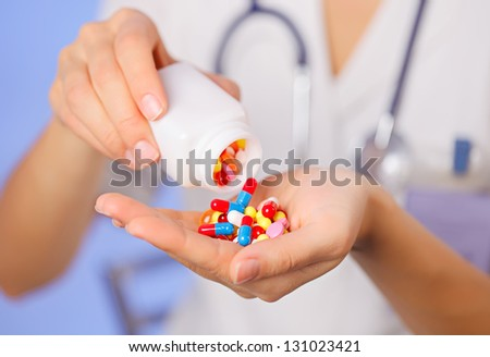 Pills, tablets and drugs pouring from bottle in doctor's hand on blue background - stock photo