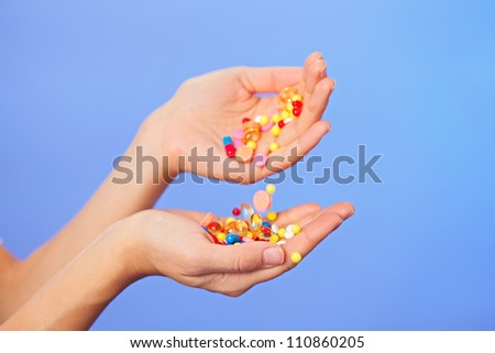 Pills, tablets and drugs pouring in doctor's hands on blue background - stock photo