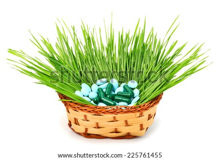 Pills, tablets and wheat grass in the basket on white - stock photo