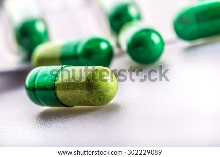 Pills. Tablets. Capsule. Heap of pills. Medical background. Close-up of pile of yellow green  tablets - capsule. Pills and tablets.Green background. - stock photo