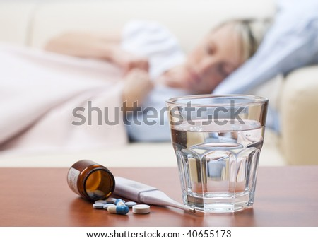 Pills, thermometer and water with girl in bed in background - stock photo