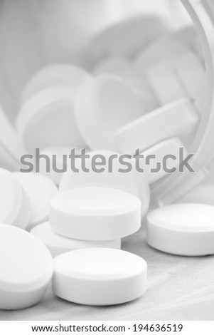 Pills - This is a high contrast black and white shot of prescription pills spilling out of a bottle. Shot with a shallow depth of field. - stock photo
