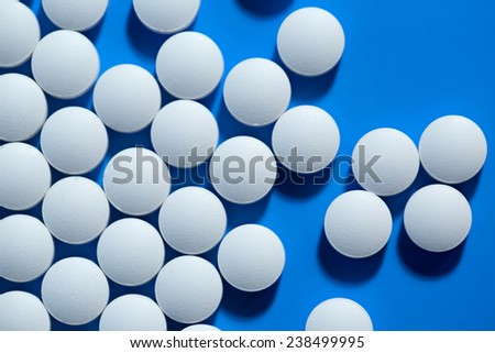 pills. White medical pills on blue background - stock photo