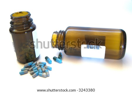 Pills with bottles isolated on white - stock photo