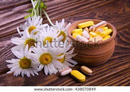 Pills with camomile on wooden background - stock photo